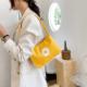 kobieta z żółtą torbą ze stokrotką na ramieniu